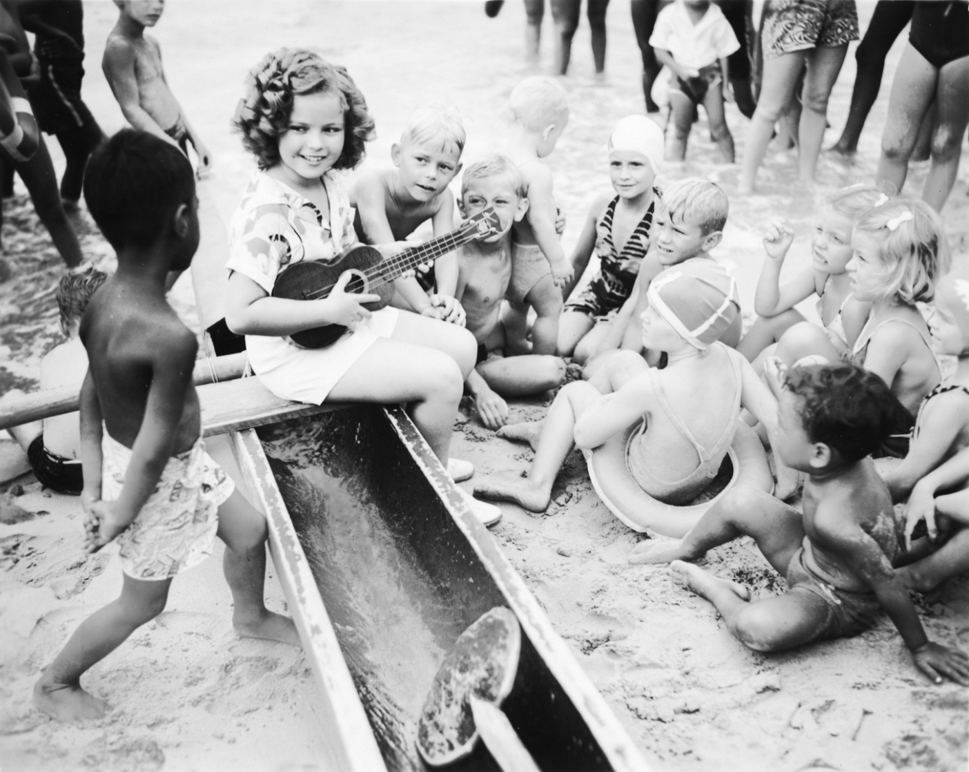 Shirley Temple, wearing an early Kabe crepe aloha shirt, playing her 'ukulele with the local children on Waikiki Beach. Photo courtesy of the Bishop Archives