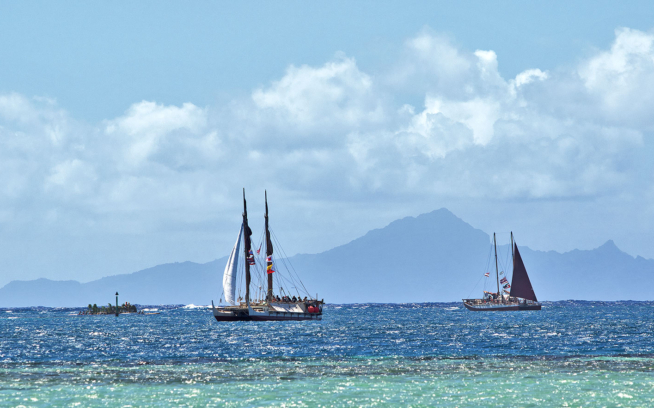With the wind in the high twenties and minimal sail up, Hōkūle'a and Hikianalia sail into Te Ava Mo'a, the Sacred Pass to Taputapuātea. Photo: John Bilderback