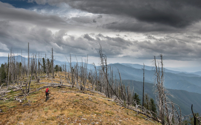 Chris Shalbot races the weather above Big Hole Pass as foreboding clouds gather in the distance. Photo: Scott Rinckenberger