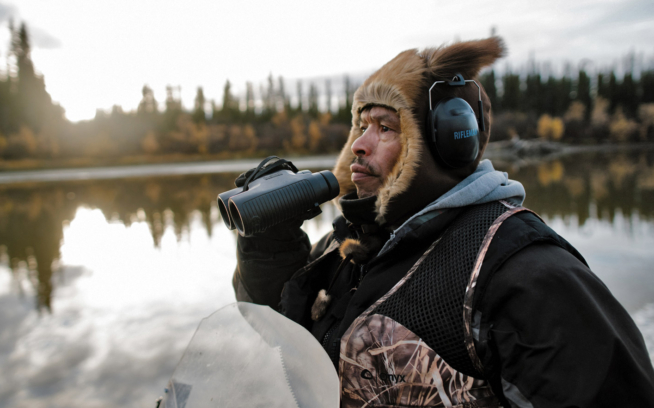 Levi Ginnis Jr. scouts the area along the Yukon River in search of moose. The hunt and the stories of Gwich'in families taking a stand to protect the Arctic National Wildlife Refuge are the main focus of the film Welcome to Gwichyaa Zhee. Photo: Greg Balkin