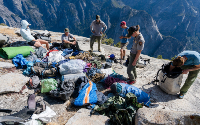 The volunteer team, made up of climbing rangers, Climber Stewards and volunteers, look at the massive pile of trash amassed from one of the many caches atop El Capitan. Photo: Eric Bissell