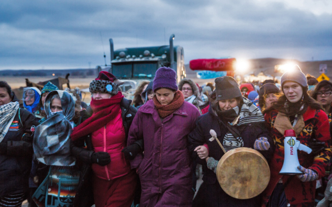 To the barricades. A women's march reached a police blockade on the Standing Rock Sioux Reservation, North Dakota, in 2016. The #NoDAPL protests focused on Indigenous rights but also the reckoning we'll all face as the climate crisis intensifies: Do we defend oil companies—or fresh water? Photo: Colin McCarthy