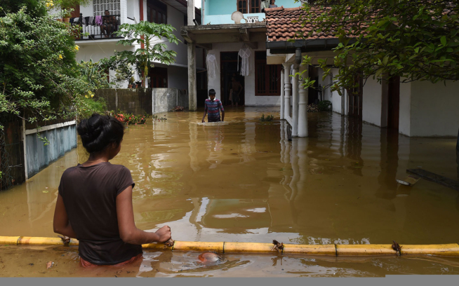 Sri Lankans outside flooded homes in Kaduwela. The massive storm that hit Sri Lanka in May of 2017 triggered the worst flooding and landslides in 14 years in the southern and western parts of the island. Extreme weather events like this one are increasing in number and strength due to human-caused climate change. Photo: Ishara S. Kodikara/AFP/Getty Images