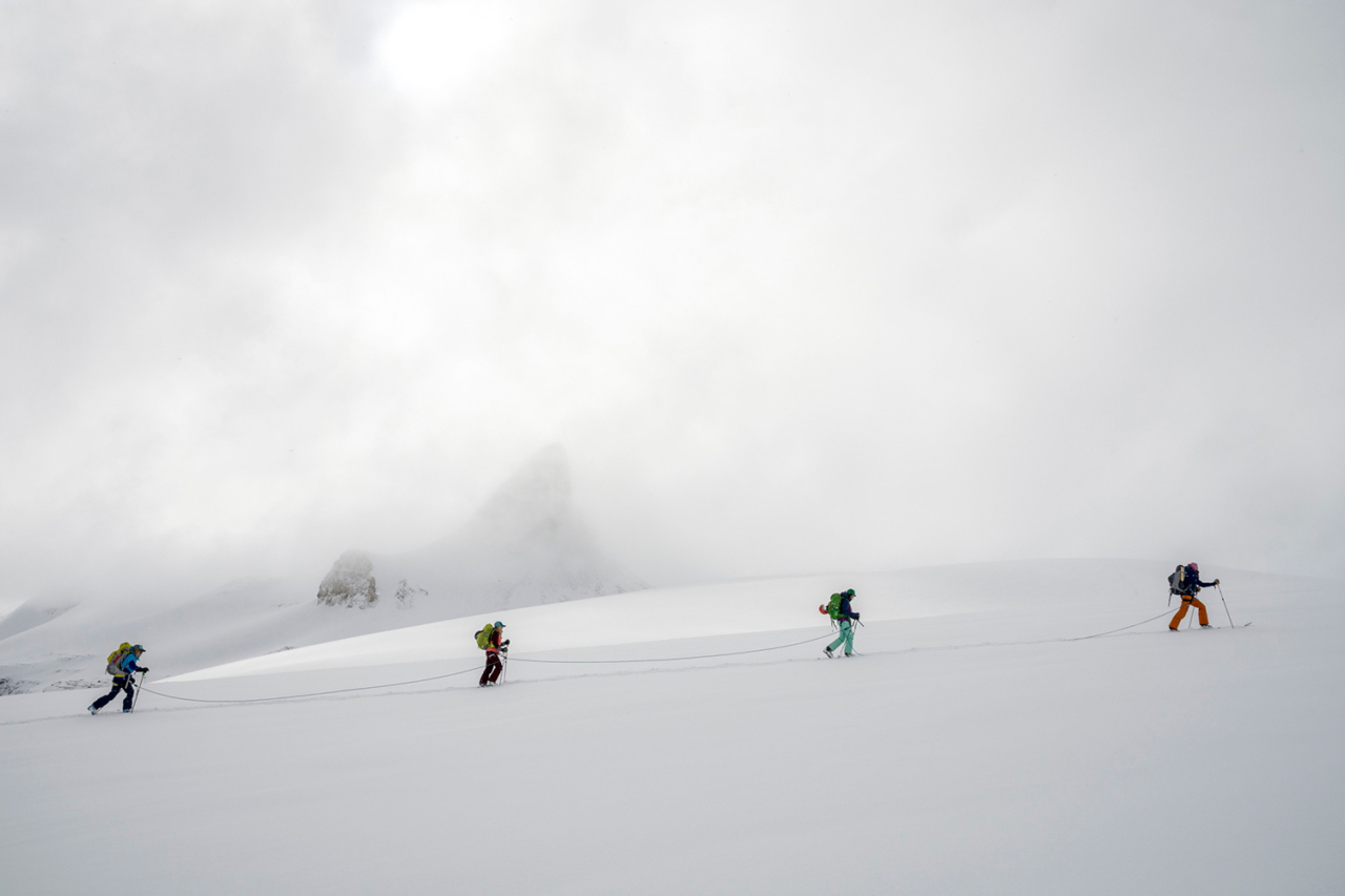 """Cresting toward a high pass on the Bow Glacier, the team traverses below the iconic Saint Nicholas Peak. After several stormy days, the clouds were just beginning to recede, the mountains shed their shrouds, and we knew that our young """"powderhounds"""" would soon be sniffing out worthy ski lines. Photo: Kennan Harvey"""