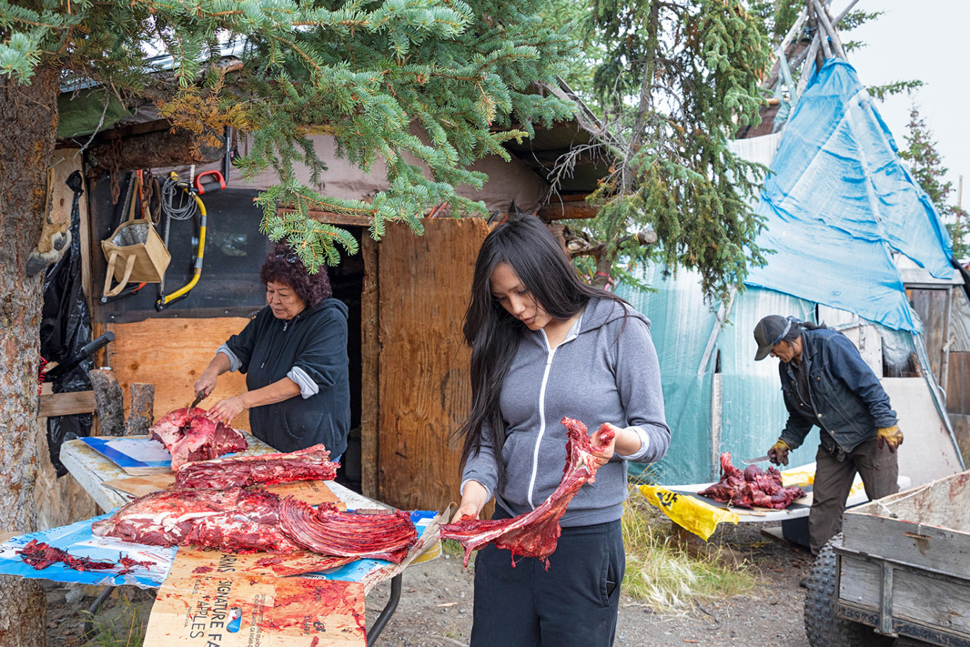 The Gilbert family and friends cut up caribou meat at their home in Vashrąįį K'ǫǫ, Alaska. Opening up the Refuge to extractive industries threatens this Gwich'in tradition. Photo: Keri Oberly