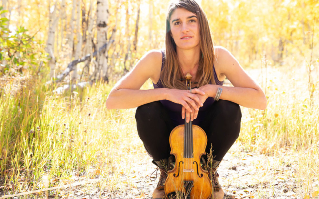 Lizzy Plotkin amongst the aspens with her Lackey five-string fiddle. Photo: Lydia Stern