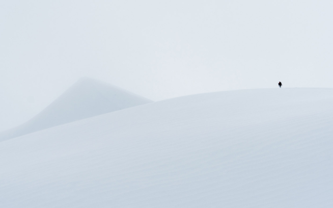 Ryland Bell hikes to the top of a glacier in northwestern British Columbia under fast-moving clouds. After a short wait in a whiteout, the skies cleared somewhat, and he was able to drop into wide open powder turns. Photo: Colin Wiseman